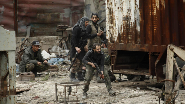 Islamist rebel fighters walk with their weapons during what they said was a takeover of the Furn Al-Ali building that was under control by the Syrian regime in Ramouseh, an area located beside Aleppo Artillery school